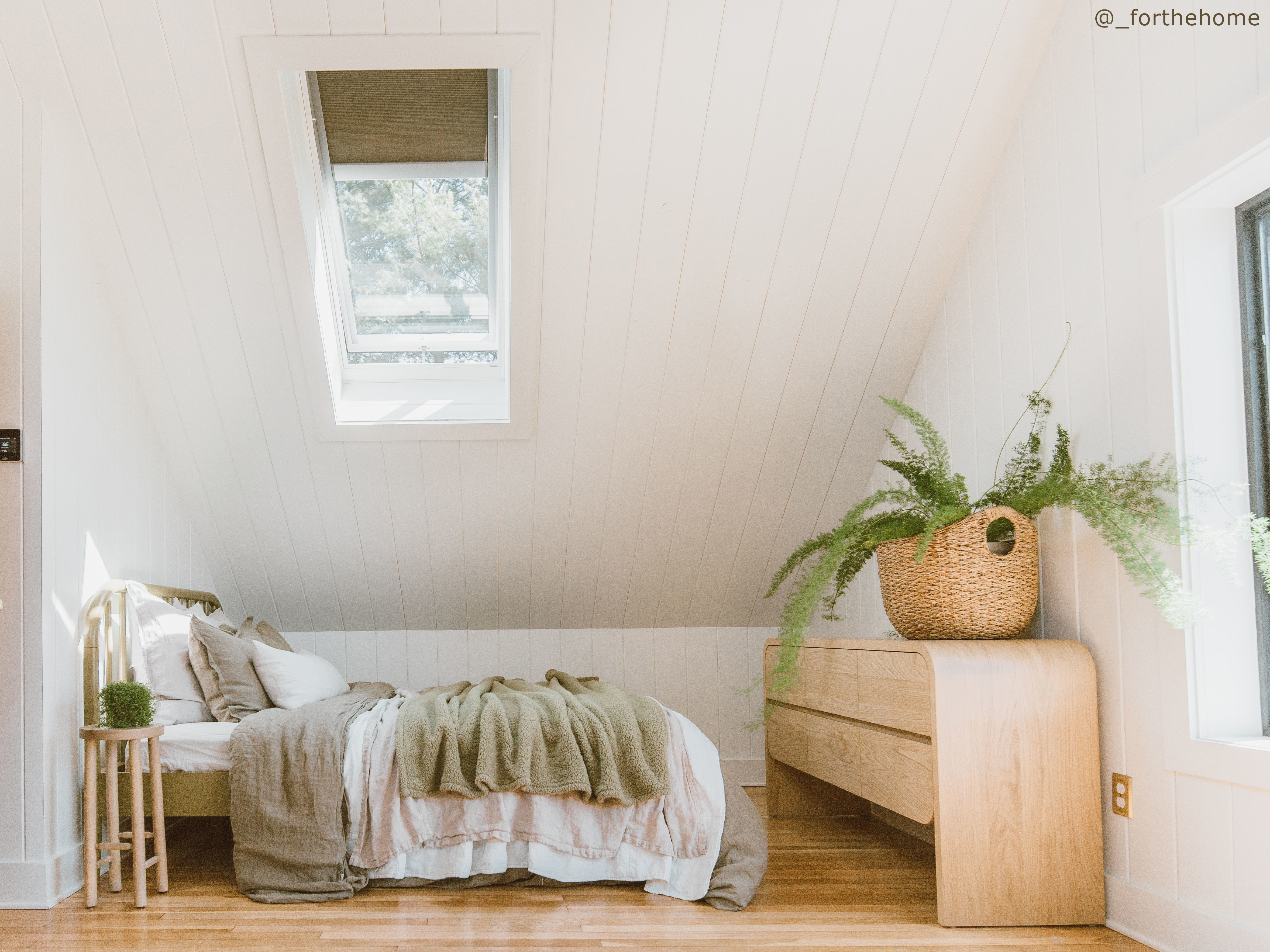 bedroom-with-natural-wood-floors-white-shiplap-and-skylight